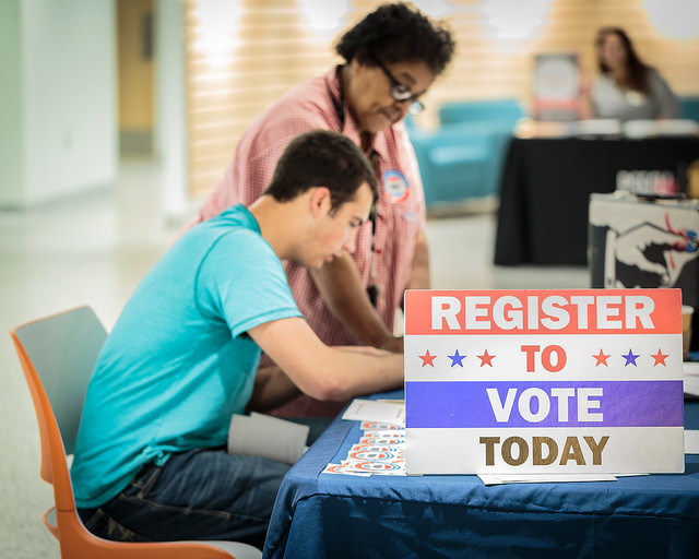 Image of two volunteers sitting behind a table with the sign, Register to Vote Today